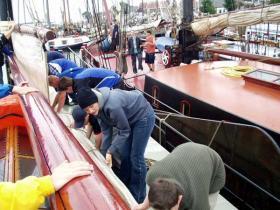 Das erste Mal holen wir die Segel nach dem schweren Sturm ein und packen sie im Hafen zusammen.