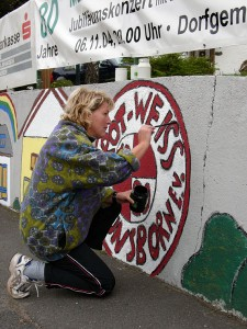 Frau Bozsik-Ose legt letzte Hand an ein Logo des Rot-Weiß Hüns